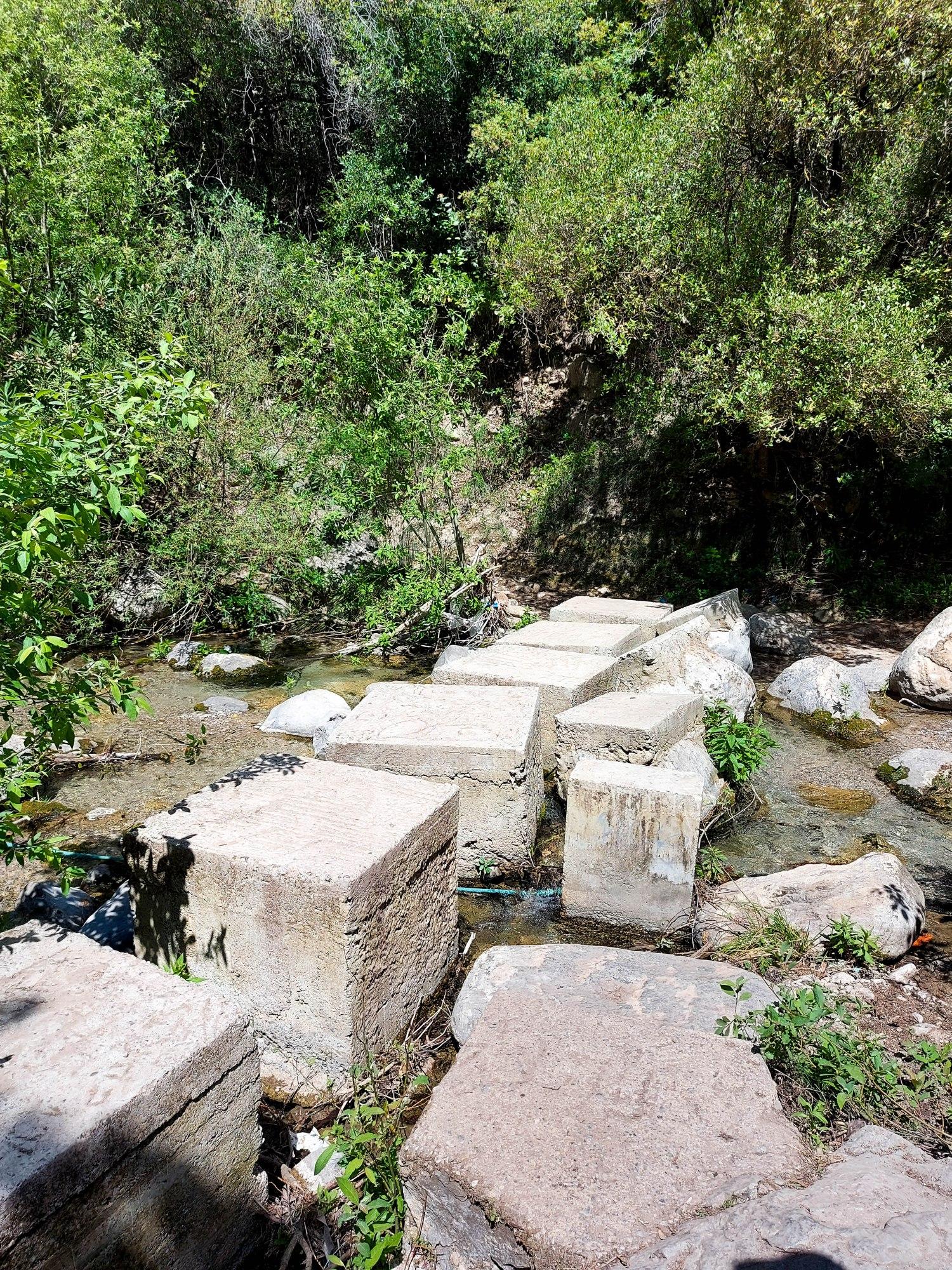 De gros bloc de pierre sont disposé côte à côte pour permettre au randonneur de traverser le ruisseau
