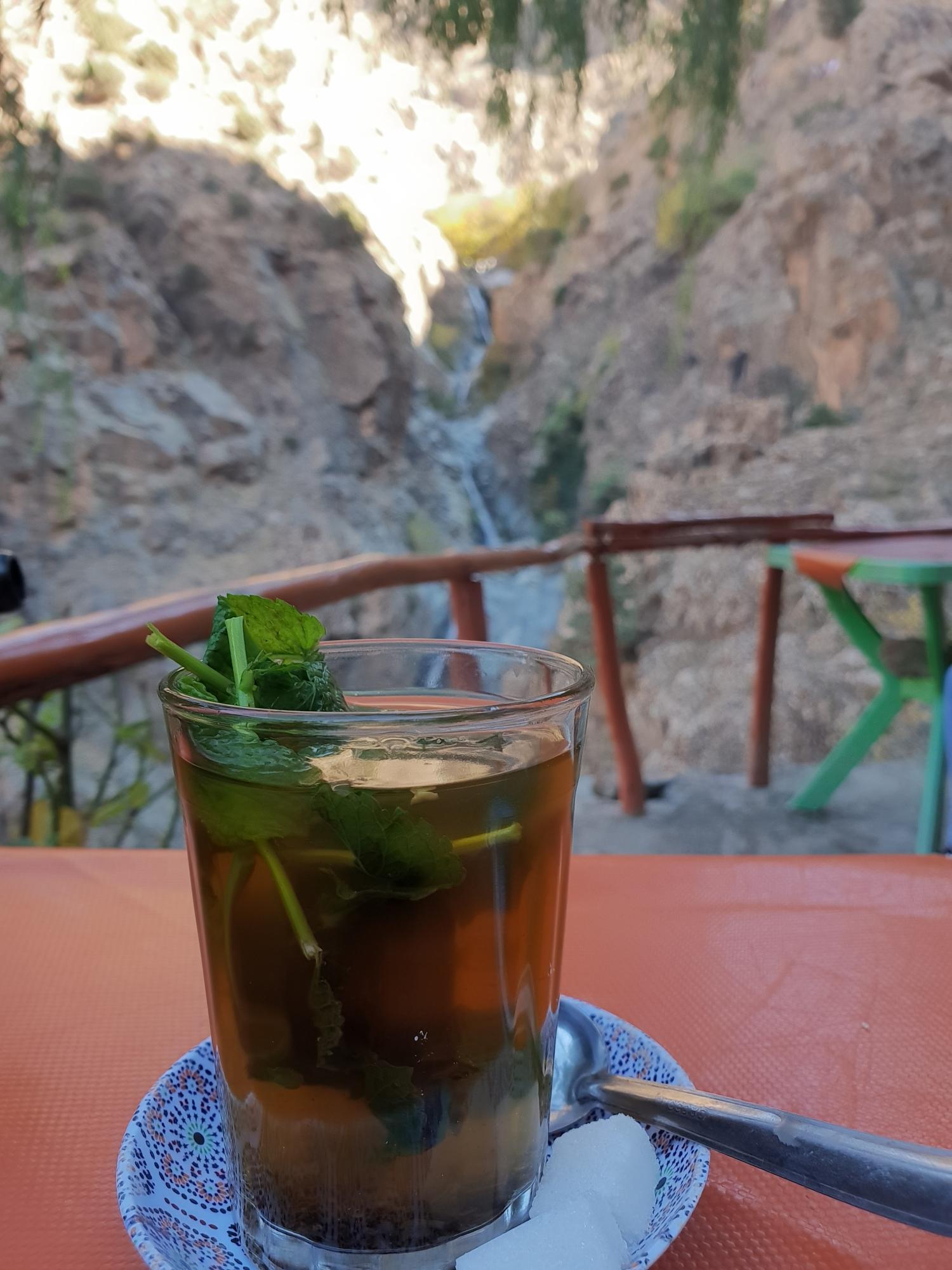 Un verre de thé marocain avec comme arrière plan les cascades de Setti-Fatma